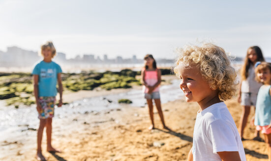 Happy little boy on the beach with other children standing in the background - MGOF02833