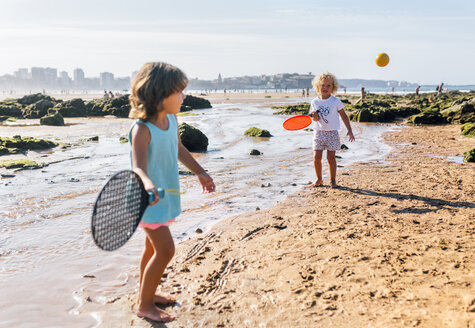 Little boy and girl playing beach paddles on the beach - MGOF02839