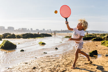 Little boy playing beach paddles on the beach - MGOF02845