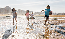 Group of five children running together on the beach - MGOF02848