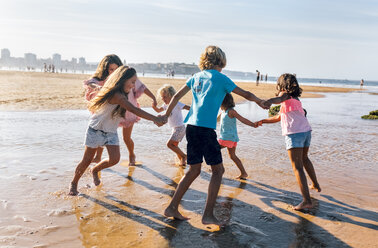 Group of six children playing ring-a-ring-a-roses on the beach - MGOF02851