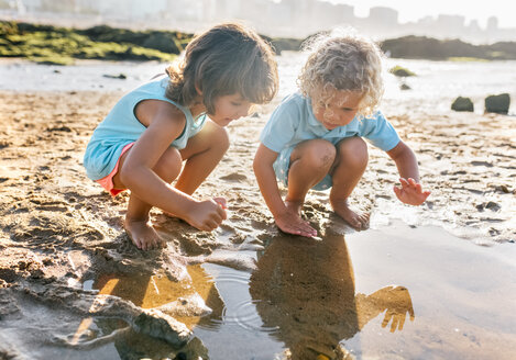 Little boy and girl playing together on the beach - MGOF02857