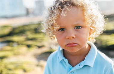 Portrait of little boy pouting mouth on the beach - MGOF02860