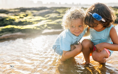 Little boy and girl playing together on the beach - MGOF02863