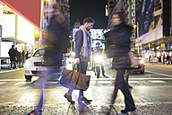 Man holding bag and cell phone crossing a street at night - ABZF01813