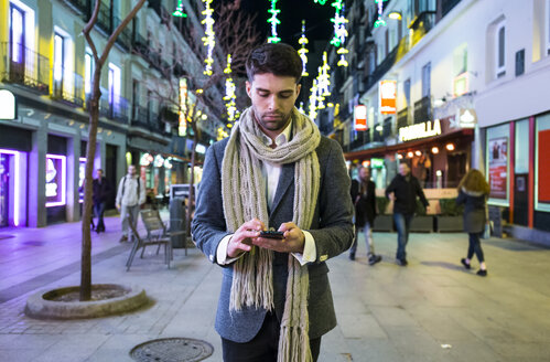 Man using his cell phone in the city at night - ABZF01819