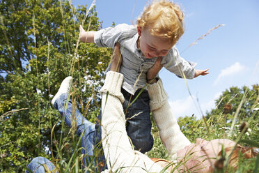 Mother lifting up happy son in meadow - FSF00664