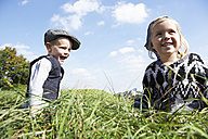 Two happy children sitting in meadow - FSF00670