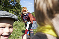 Happy mother playing with children in meadow - FSF00676