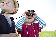 Boy and girl with binoculars on meadow - FSF00682