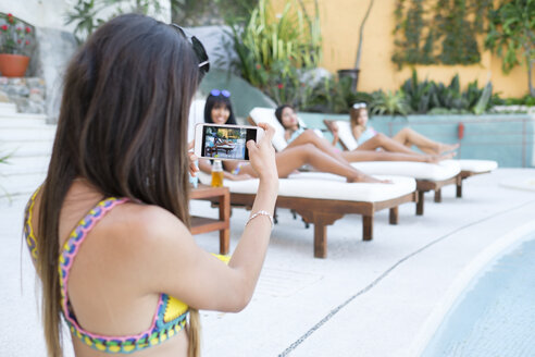 Young woman taking cell phone picture of friends at the poolside - ABAF02142