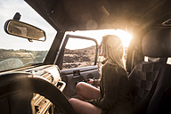 Woman getting on car at sunset - SIPF01385