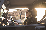 Woman sitting in car at sunset - SIPF01388