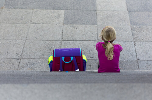 Back view of little girl with school bag sitting on stairs - JFEF00841