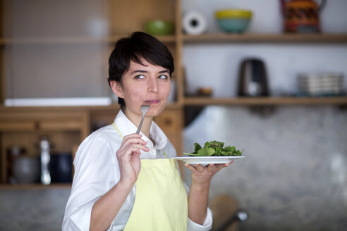 Portrait of young woman tasting salad in the kitchen - SGF02103
