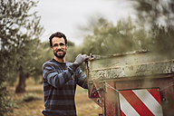Spain, portrait of smiling man working in olive grove - JASF01497