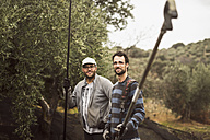Spain, portrait of two smiling workers with working tools in olive grove - JASF01503