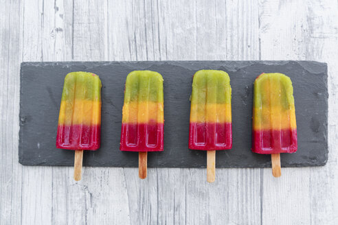Row of four homemade fruit smoothie ice lollies on slate - SARF03143