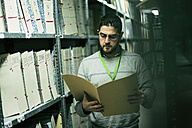 Portrait of serious man reading documents in an archive - JASF01506