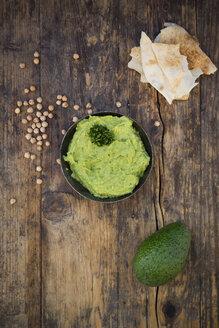 Bowl of avocado hummus, avocado, chick-peas and flat bread on dark wood - LVF05821