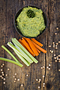 Bowl of avocado hummus, chick-peas and crudites on dark wood - LVF05824