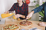 Young couple eating pizza and drinking juice for lunch, laptop standing on table - RTBF00620