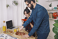Young couple eating pizza and drinking juice for lunch, woman taking pictures with smart phone - RTBF00623