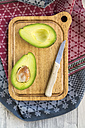 Sliced avocado and knife on chopping board - SARF03156