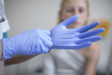 Doctor putting on blue latex gloves - ZEF12612