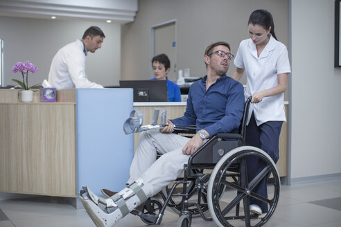 Nurse pushing patient in wheel chair through hospital - ZEF12630