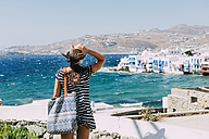Greece, Mykonos, back view of tourist looking to Little Venice - GEMF01465