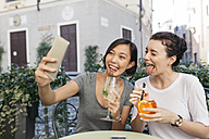 Italy, Padua, two young women pulling funny faces  while taking selfie at sidewalk cafe - ALBF00074