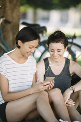 Two friends sitting in city park listening music together with earphones - ALBF00104