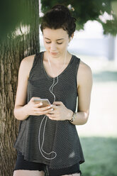 Young woman listening music with earphones in summer - ALBF00107
