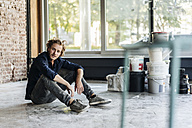 Man sitting on floor in unfinished room - KNSF00884