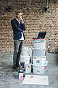 Businessman standing in room with laptop and paint buckets - KNSF00887