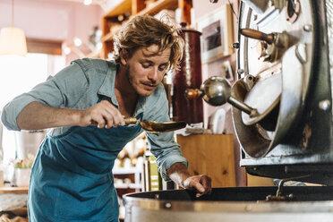 Coffee roaster in his shop examining coffee beans - KNSF00893