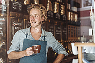 Smiling coffee roaster in his shop drinking cup of coffee - KNSF00908