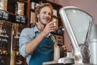 Coffee roaster weighing coffee in his shop - KNSF00911
