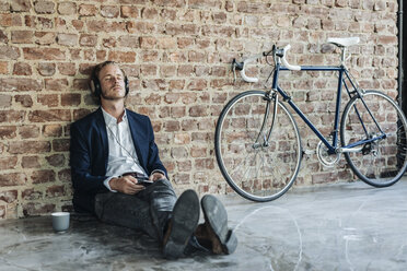 Relaxed man with headphones leaning against brick wall - KNSF00932