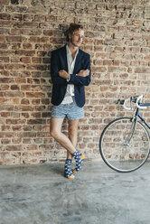 Businessman standing at brick wall wearing jacket and underwear - KNSF00935