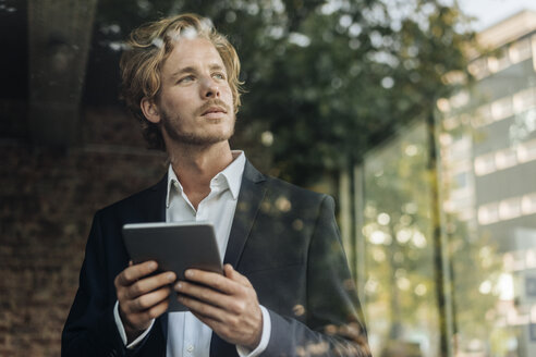 Businessman with tablet looking away - KNSF00941