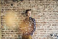 Portrait of smiling man at brick wall using laptop - KNSF00965
