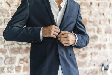 Close-up of of businessman buttoning jacket - KNSF00971