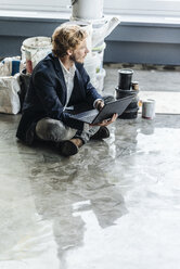 Businessman sitting on floor with laptop and paint buckets - KNSF00974