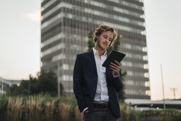 Businessman outdoors looking at tablet - KNSF00980