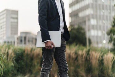 Businessman holding laptop outdoors - KNSF00983