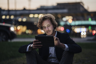 Businessman sitting on meadow at dusk using tablet - KNSF00986