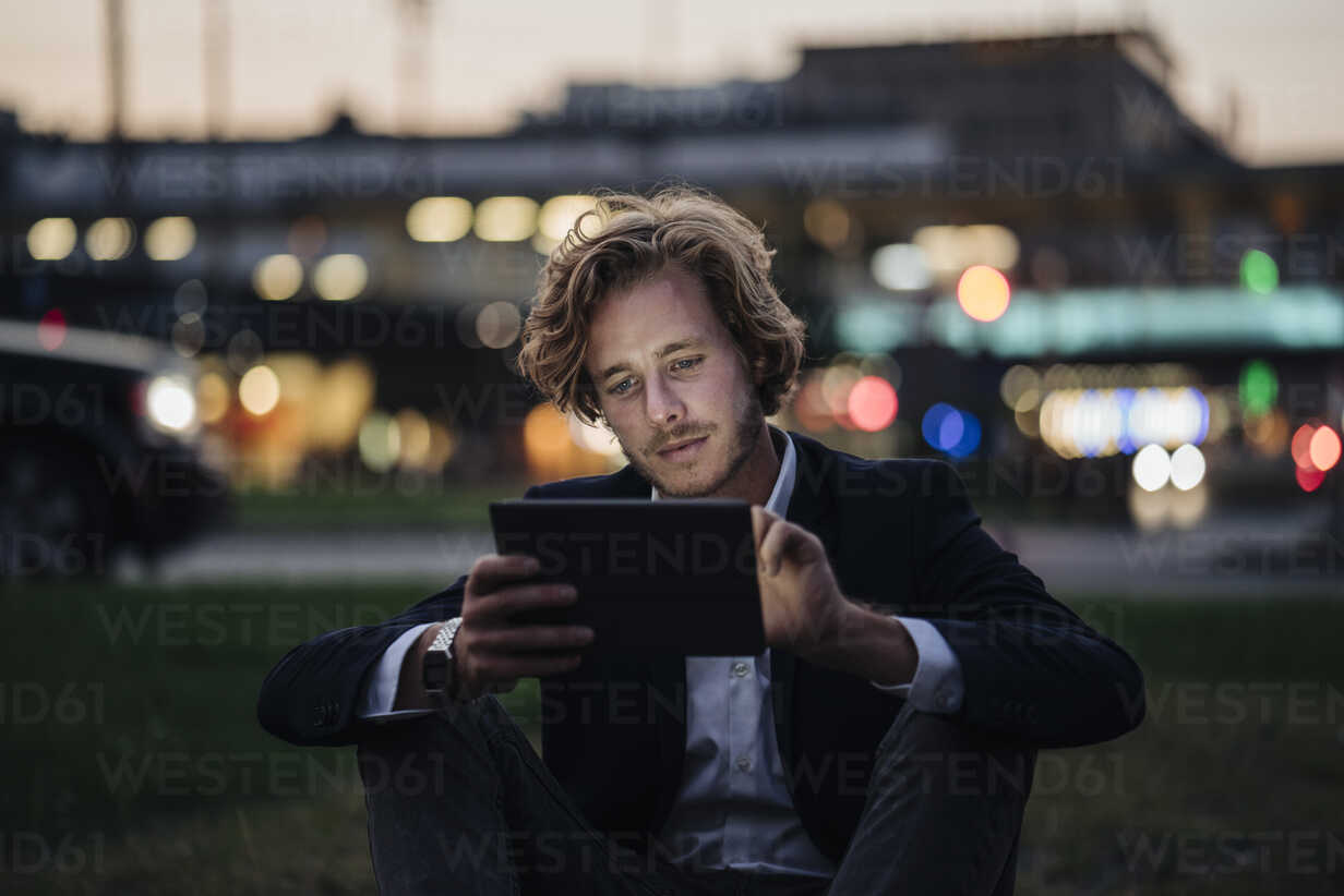Businessman sitting on meadow at dusk using tablet - KNSF00986 - Kniel Synnatzschke/Westend61