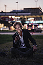 Smiling businessman sitting on meadow at dusk with cell phone and earphones - KNSF00989